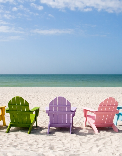 multi-colored chairs on a beach